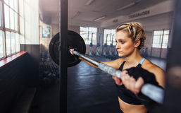 Young woman working out at the gymnasium using weight bar. Royalty Free Stock Photography