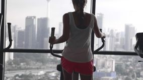 Woman working out in gym. Young woman working out hard in sports club.Attractive girl at the gym riding on the spinning bike with great view over city.Active