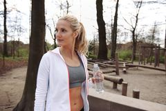 Young woman after working out at a park. Young woman in park with water bottle looking away. Fitness woman relaxing after training session in nature Stock Image