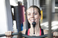 Young woman working out on weight-lifting training ma Stock Images