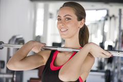 Young woman working out on weight-lifting training ma Stock Photo
