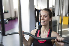 Young woman working out on weight-lifting training ma Royalty Free Stock Photos