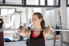 Young woman working out on weight-lifting training ma Stock Photos