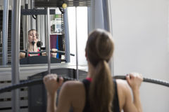 Young woman working out on weight-lifting training ma Royalty Free Stock Images