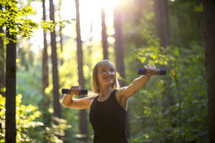Young woman working out with weights. Smiling happy fit young woman working out with weights in a wooded garden or park under the warm glow of the sun in a Stock Image