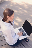 Young woman working outdoors on a laptop Royalty Free Stock Image