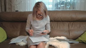 Young woman working with papers and cellphone, calculating numbers stock video footage