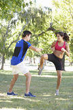 Young Woman Working With Personal Trainer In Park Royalty Free Stock Photography