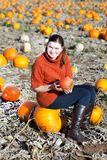 Young woman working on pumpkin field Royalty Free Stock Image