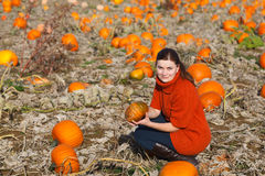 Young woman working on pumpkin field Royalty Free Stock Photography