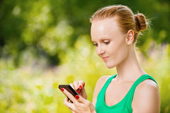 Young woman working with smartphone Royalty Free Stock Photography