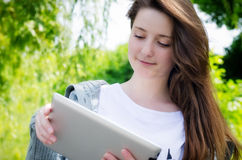 Young woman working on a tablet in the park. Low angle view of an attractive casual young woman working on a touch screen tablet in the park Royalty Free Stock Images