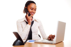 Young woman working and talking on the phone Stock Images