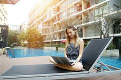 Young woman working uses new laptop pc outdoors remotely as freelancer close to swimming pool and apartment building. Young female woman working with new laptop Royalty Free Stock Photography