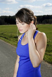 Young woman in workout clothes with headphones. Young woman outdoors in workout clothes with headphones Stock Images