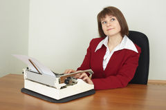 Young woman works on an ancient typewriter Royalty Free Stock Photography