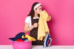 Young woman works as maid, wears t shirt, brown apron and hair band, standing near pink basin with clean linen isolated on rose royalty free stock image