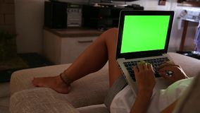 A young woman works on her laptop with the green screen at home sitting on the sofa in her living room. A young woman works on her laptop with the green screen stock footage