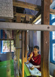 Young woman works inside home on a hand loom. Stock Photos