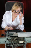 Young woman works with an old typewriter. Royalty Free Stock Photos