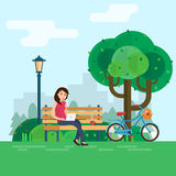 Young woman works in park with computer on bench under tree. Royalty Free Stock Image