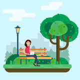 Young woman works in park with computer on bench under tree. Stock Photo