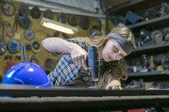 young woman using screwdriver in a workshop
