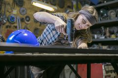 young woman in a workshop using screwdriver