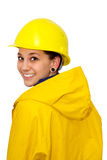 Young woman in workwear. Young woman wearing a yellow helmet and raincaot. Isolated on white background stock photography