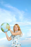 Young woman with world globe. Happy young blond woman with blue globe, blue sky and cloudscape background Stock Images
