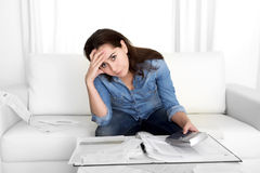 Young woman worried at home in stress accounting bank papers with calculator Royalty Free Stock Photos