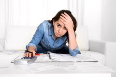Young woman worried at home in stress accounting desperate in financial problems. Young woman worried at home in stress at living room accounting debt bills Royalty Free Stock Photography