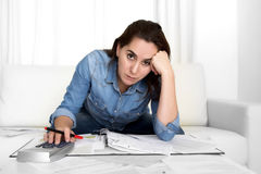 Young woman worried at home in stress accounting desperate in financial problems. Young woman worried at home in stress at living room accounting debt bills Stock Photo