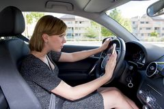 Worried and stressed woman driving car while texting on mobile phone distracted Stock Photo