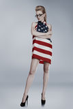 Young woman wrapped in american. Young attractive blond woman wrapped in american flag Royalty Free Stock Photo