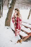 Young woman wrapped in blanket drinking hot tea in snowy forest Royalty Free Stock Image