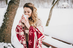 Young woman wrapped in blanket drinking hot tea in snowy forest Royalty Free Stock Photography