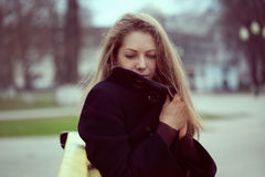 Young woman wrapped in a coat from the cold Stock Images