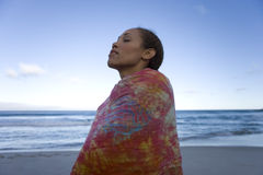 Young woman wrapped in sarong on beach, eyes closed, low angle view Royalty Free Stock Image