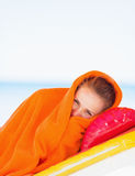 Young woman wrapped in towel laying on sunbed Stock Photo