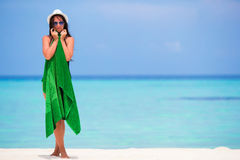 Young woman wrapped in towel on white sandy beach Stock Images