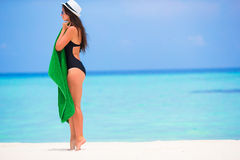 Young woman wrapped in towel on white sandy beach Stock Photos