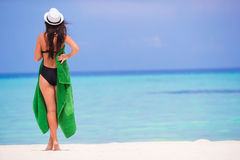 Young woman wrapped in towel on white sandy beach Stock Photography