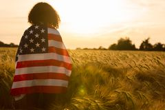 Young Woman Wrapped in USA Flag in Field at Sunset Stock Photo