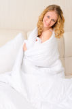 Young woman wrapped in white blanket Stock Images