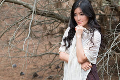 Young woman wrapped in a white scarf stays in forest Stock Photos