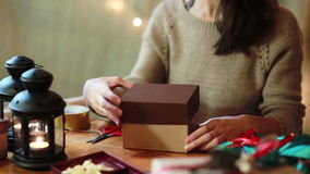 Young Woman Wrapping Christmas Gifts At Home. Young Woman Wrapping Christmas Gifts With Brown Paper At Home stock video footage