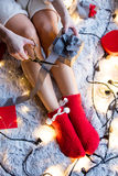 Young woman wrapping gift. Photo of young woman wrapping gift on the warm blanket full of garland and other gifts Stock Photo