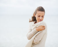 Young woman wrapping in sweater on coldly beach. Young woman with long hair wrapping in sweater on coldly beach stock photography