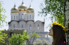 Young woman in a wreath of dandelions looks at an orthodox temple, spring.  Stock Photography